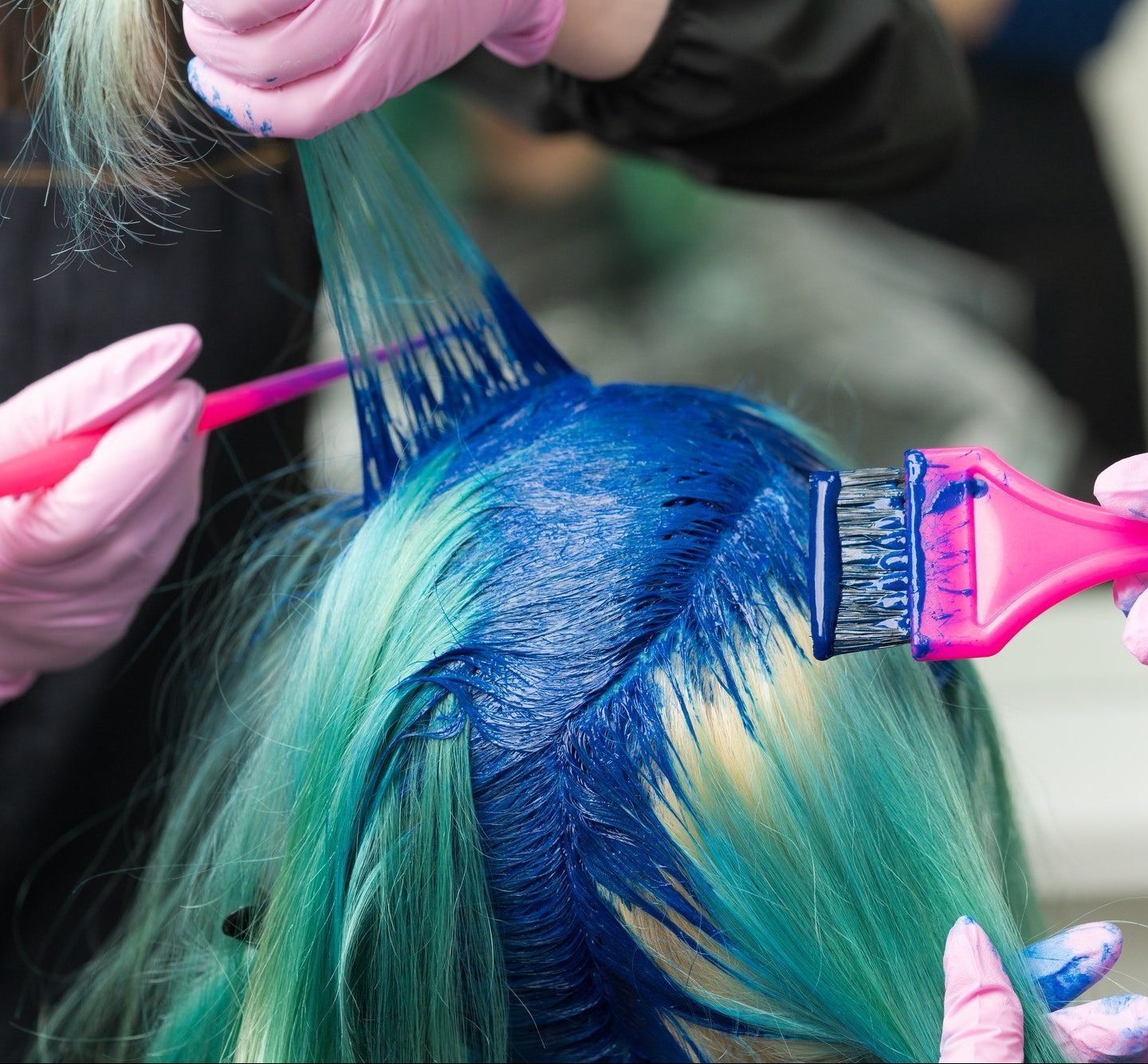Hairdressers Applying Blue Paint to Emerald Hair Color During Process of Dyeing Hair in Unique Color